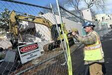 (Arnold Gold-New Haven Register)  Wallace Hitchcock puts up construction signs where the first demolition takes place at Church Street South Apartments in New Haven on 3/21/2016.