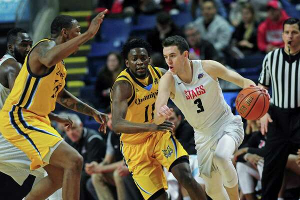 Fairfield University's Tyler Nelson gets the ball past Quinnipiac's Alain Chigha in their MAAC Men's Basketball game Friday, February 17, 2018, at Webster Arena in Fairfield, Conn.