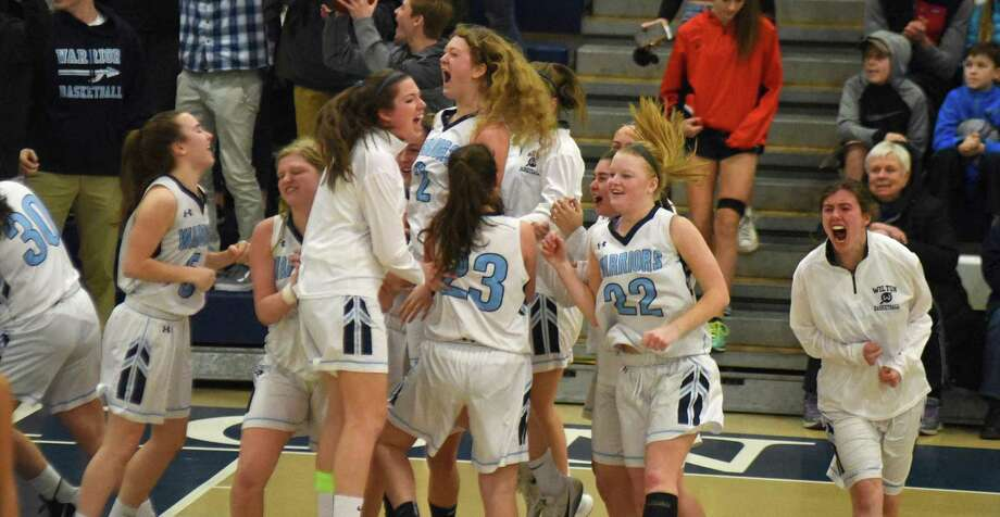 Members of the Wilton girls basketball team react after holding off Staples for a 57-53 win during Saturday's FCIAC girls basketball quarterfinal at the Zeoli Field House in Wilton. Photo: John Nash/Hearst Connecticut Media