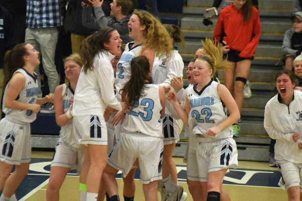Members of the Wilton girls basketball team react after holding off Staples for a 57-53 win during Saturday's FCIAC girls basketball quarterfinal at the Zeoli Field House in Wilton.
