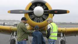 Russ Renaud of Hondo with the Tex Hill Wing of the Commemorative Air Force (right) chats with Richard Ponke (left) and his 10-year-old son, Casey, in front of a 1942 SNJ-4 trainer during the Tet 68 Plus 50 Vietnam War Remembrance at Stinson Municipal Airport on Saturday, Feb. 17, 2018. The plane, though not from the Vietnam era, is part of the Tex Hill Wing squadron, now based at Stinson. The group usually organizes World War II events; this was the first one focused on recognizing veterans of the Vietnam War. The free event featured numerous displays and exhibits of military gear, weapons and vehicles. Ponke said his son is a big military history buff so the event was ideal for them to attend. (Kin Man Hui/San Antonio Express-News)