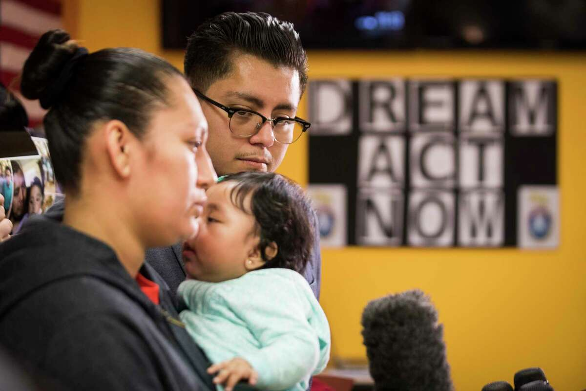 Cesar Espinosa, executive director of FIEL Houston listens to Marcela Rivera, 31, speak to the press about her husband Carlos Gudiel who was detained January 19th, 2018 at 6:20 a.m. while he was loading his work tools in the parking lot of his apartment. ( Marie D. De Jesus / Houston Chronicle )