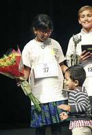 Harini Logan, winner of the 65th annual Express-News Spelling Bee, smiles as her younger brother Naren runs up to her on stage at McAllister Auditorium after the bee ended Saturday, Feb. 17, 2018. At right, second-place finisher Sam Pick looks on.