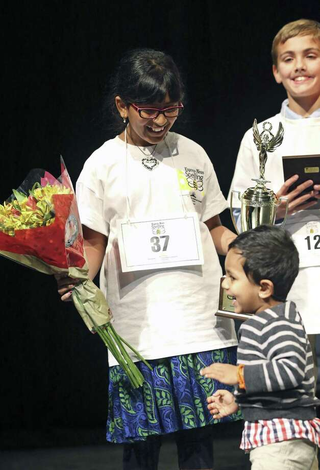 Harini Logan, winner of the 65th annual Express-News Spelling Bee, smiles as her younger brother Naren runs up to her on stage at McAllister Auditorium after the bee ended Saturday, Feb. 17, 2018. At right, second-place finisher Sam Pick looks on. Photo: Tom Reel /San Antonio Express-News / 2017 SAN ANTONIO EXPRESS-NEWS