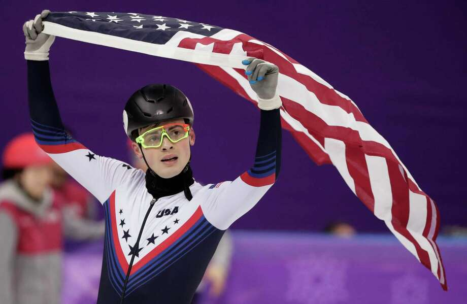 John-Henry Krueger hoists the U.S. flag for a victory lap of sorts after capturing the silver medal in the men's 1,000-meter event during short-track speedskating Saturday night. Photo: Julie Jacobson, STF / Copyright 2018 The Associated Press. All rights reserved