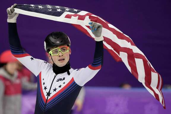 John-Henry Krueger hoists the U.S. flag for a victory lap of sorts after capturing the silver medal in the men's 1,000-meter event during short-track speedskating Saturday night.