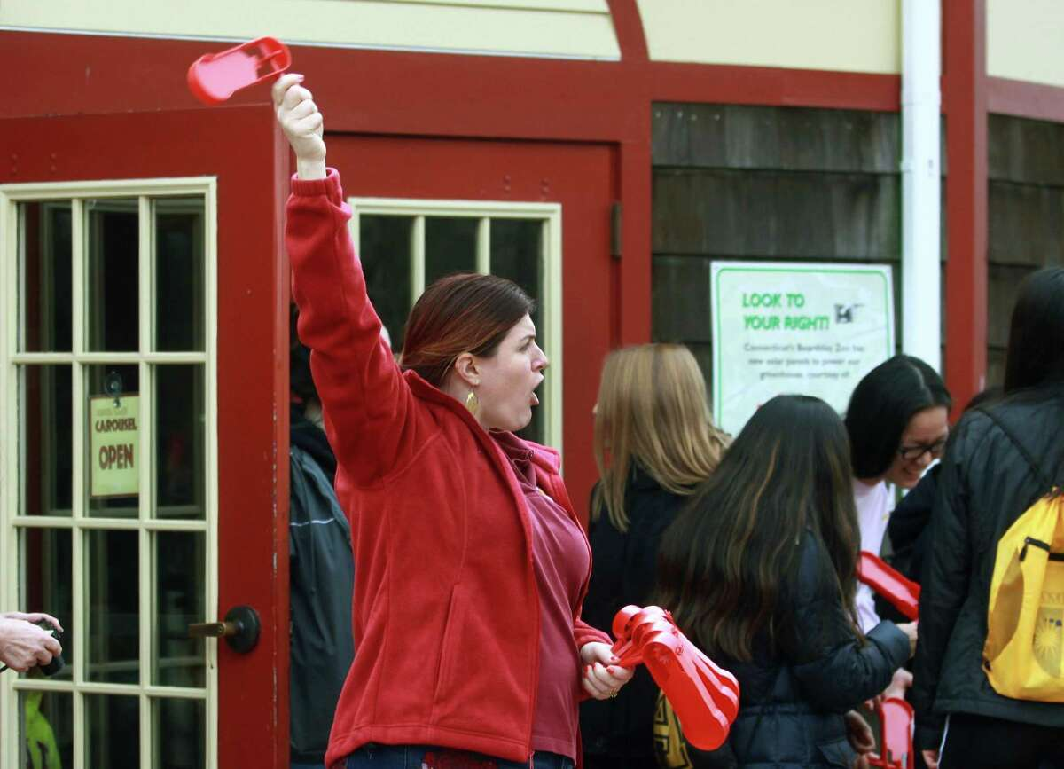Volunteer Chandra Gioiello hands out noisemakers to ward of evil spirits during Beardsley Zoo's Asian New Year celebration in Bridgeport, Conn., on Saturday Feb. 17, 2018. This year, 4716, is the year of the dog. Sone of the activities included a visit with the zoo's real dogs like Mexican wolves, red wolves, maned wolves and even a grey fox. There were also activities like fortunes, Chinese checkers, story-time and coloring.