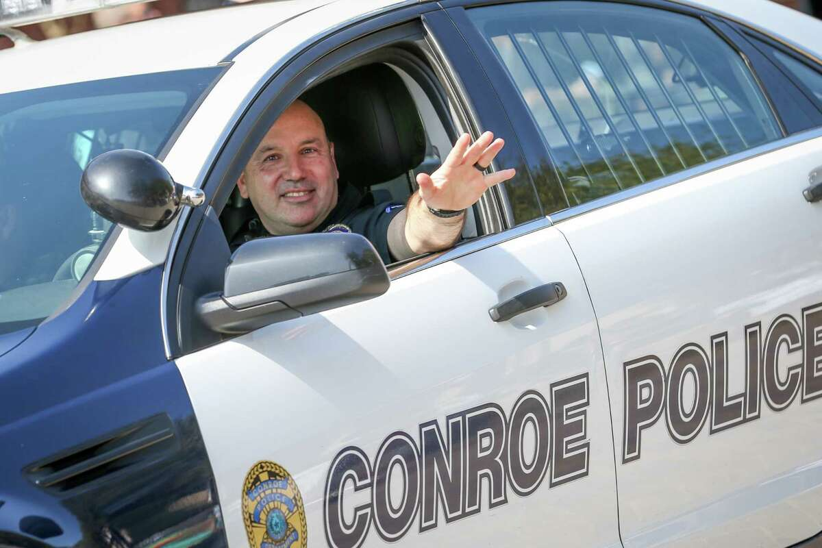 Conroe Police Officer David Burge waves while leading the 53rd annual Go Texan Parade and Stampede on Saturday in downtown Conroe.