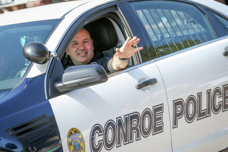Conroe Police Officer David Burge waves while leading the 53rd annual Go Texan Parade and Stampede on Saturday  in downtown Conroe. Photo: Michael Minasi, Staff Photographer / © 2017 Houston Chronicle