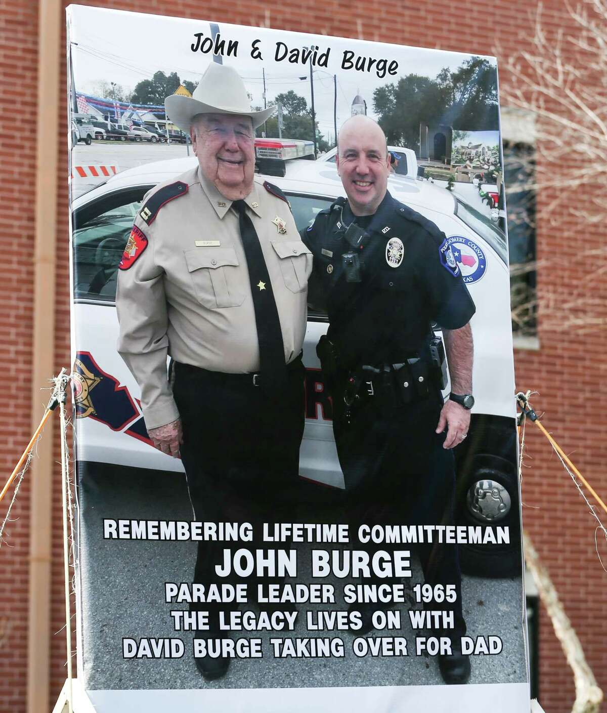 A photo of recently passed John Burge and his son David is featured during the 53rd annual Go Texan Parade and Stampede on Saturday, Feb. 17, 2018, in downtown Conroe.