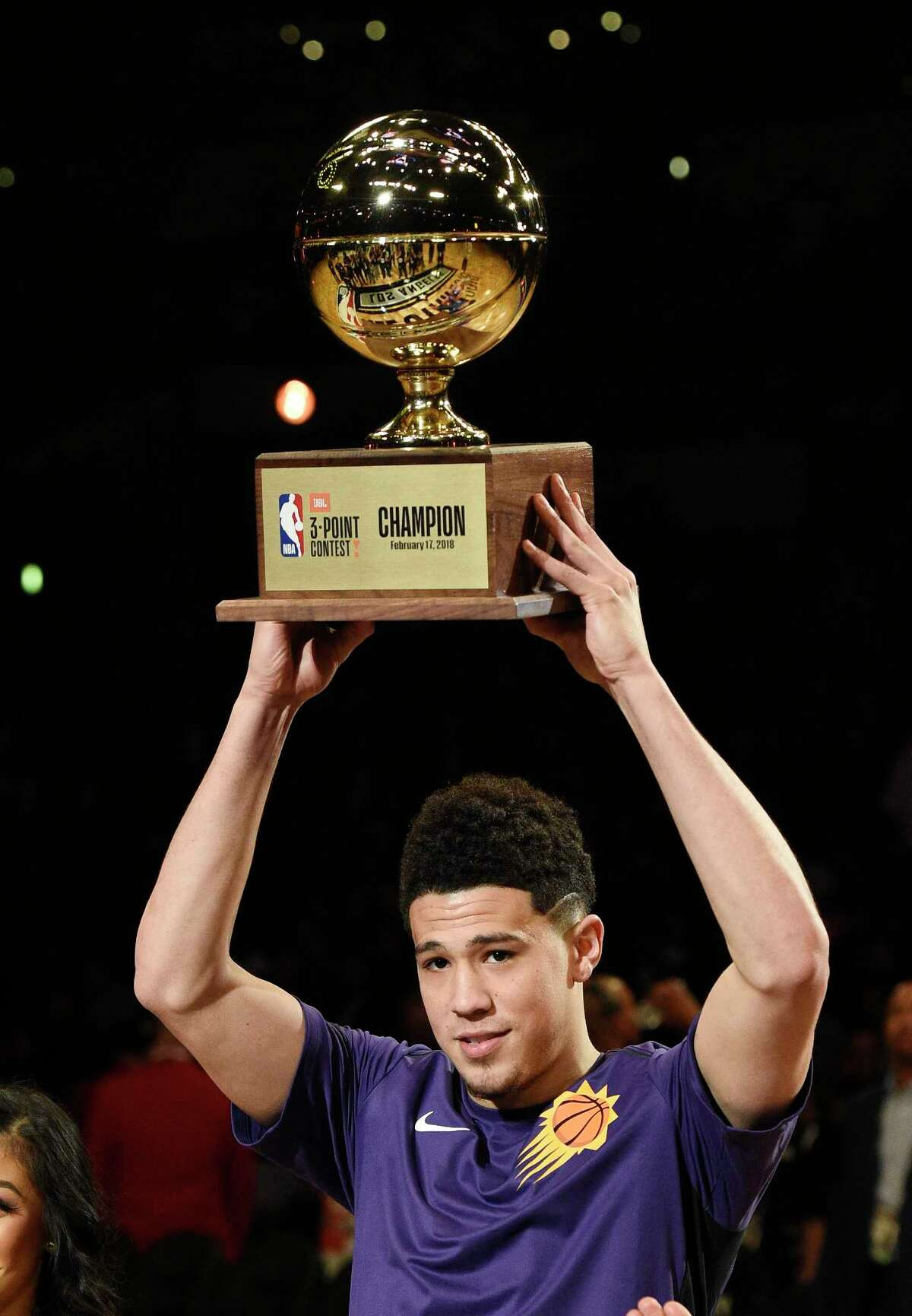 Phoenix Suns' Devin Booker holds up his trophy after winning the NBA All-Star basketball Three Point contest, Saturday, Feb. 17, 2018, in Los Angeles. (AP Photo/Chris Pizzello)