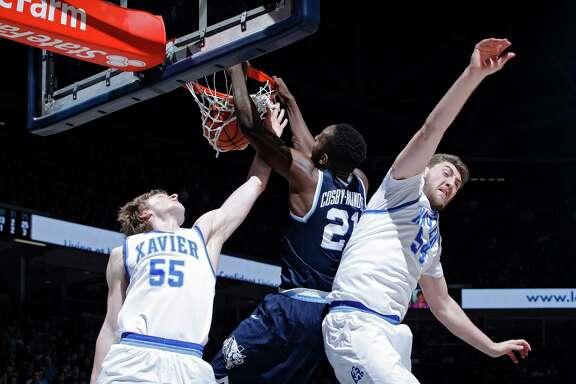 Villanova's Dhamir Cosby-Roundtree, center, splits Xavier defenders J.P. Macura, left, and Sean O'Mara for a dunk.