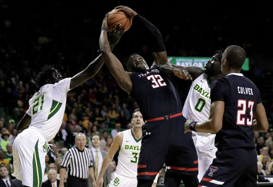 Baylor's Nuni Omot (21) and Jo Lual-Acuil Jr. (0), of Australia challenge Texas Tech's Norense Odiase (32) for control of a rebound in the first half of an NCAA college basketball game Saturday, Feb. 17, 2018, in Waco, Texas. Photo: Tony Gutierrez, AP / Copyright 2018 The Associated Press. All rights reserved.