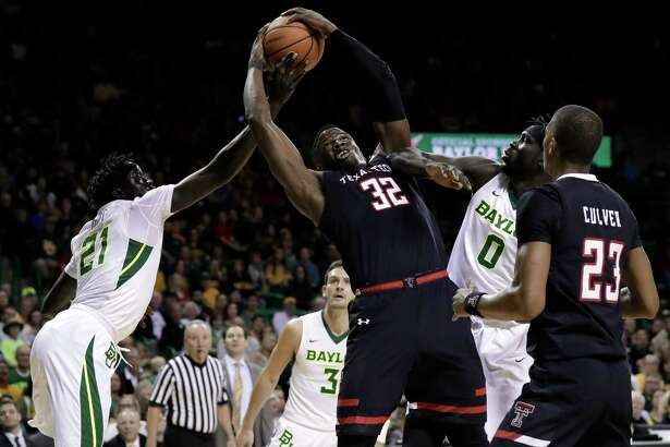 Baylor's Nuni Omot (21) and Jo Lual-Acuil Jr. (0), of Australia challenge Texas Tech's Norense Odiase (32) for control of a rebound in the first half of an NCAA college basketball game Saturday, Feb. 17, 2018, in Waco, Texas.