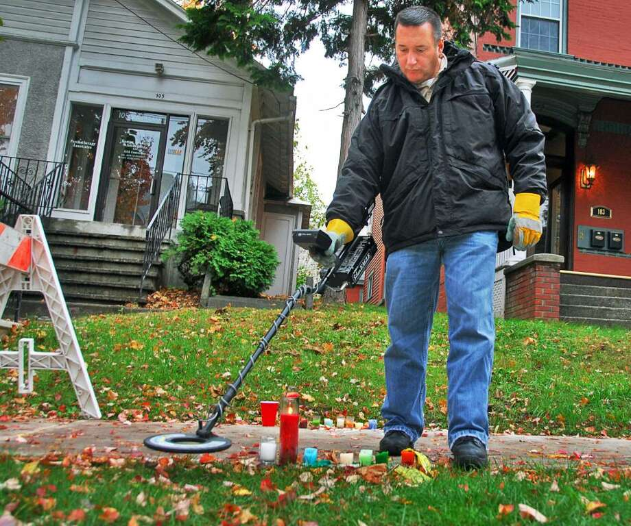 JOHN CARL D'ANNIBALE/TIMES UNION-- Albany Police Forensic unit's Victor Pizzola uses a metal detector Wednesday morning October 22, 2008, to search for evidence near the make-shift memorial for UAlbany student Richard Bailey, who was  shot - and subsequently killed  Monday night near the corner of Yates and South Lake in Albany. Photo: John Carl D'Annibale
