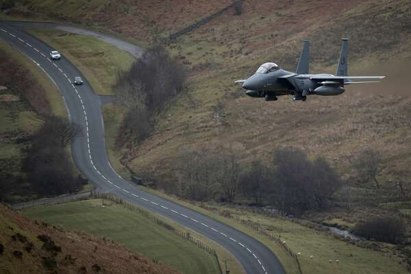 DOLGELLAU, WALES - FEBRUARY 16:  A United States Air Force F-15 fighter jet based at RAF Lakenheath speeds through the Dinas Pass, known in the aviation world as the Mach Loop on February 16, 2018 in Dolgellau, Wales. United Kingdom. The Royal Air Force and aircraft of the United States use the valleys of Snowdonia to practice low flying techniques and pilot training. The mountain peak vantage points attract aviation enthusiasts from all over the world who hope for a glimpse of their favourite military aircraft spending days waiting for the un-published and un-scheduled fly pasts.  (Photo by Christopher Furlong/Getty Images)