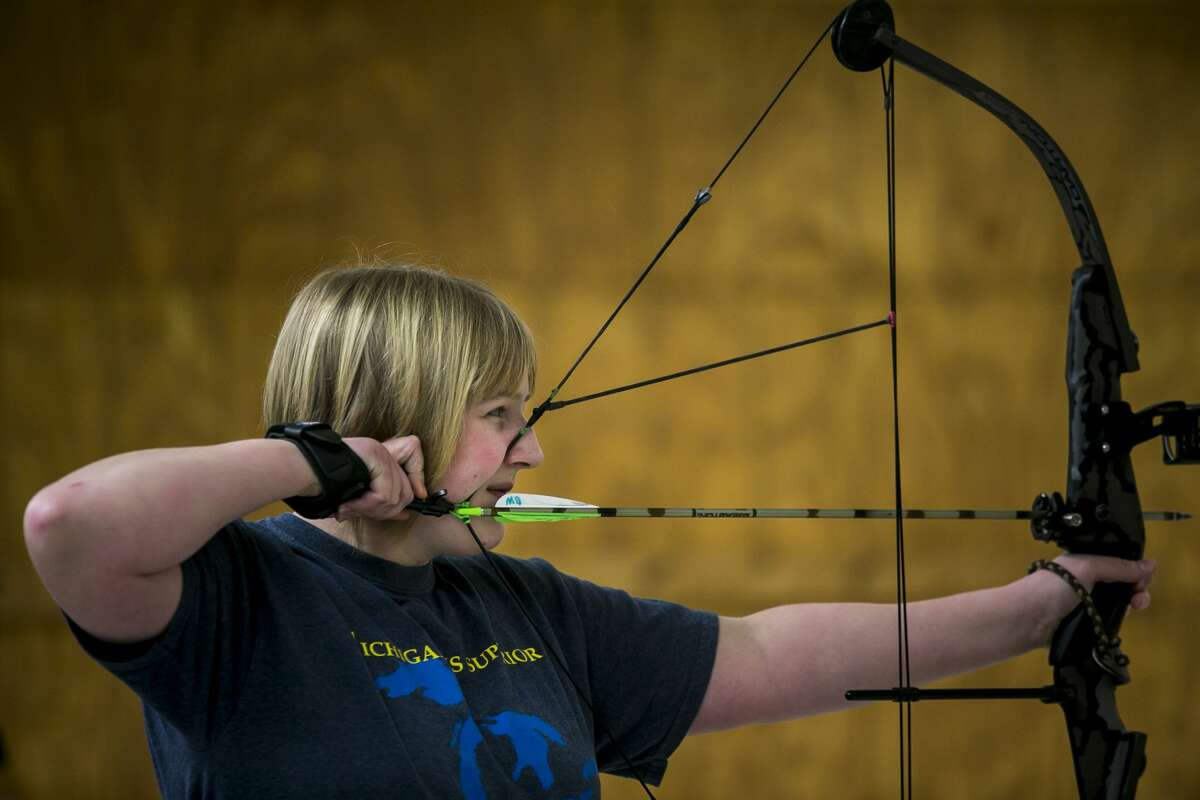 Marissa Berghuis,14, of Sanford squints as she aims during the Youth Indoor 3D shoot at Mid Michee Bowmen Saturday, Feb. 17, 2018. (Josie Norris/for the Daily News)