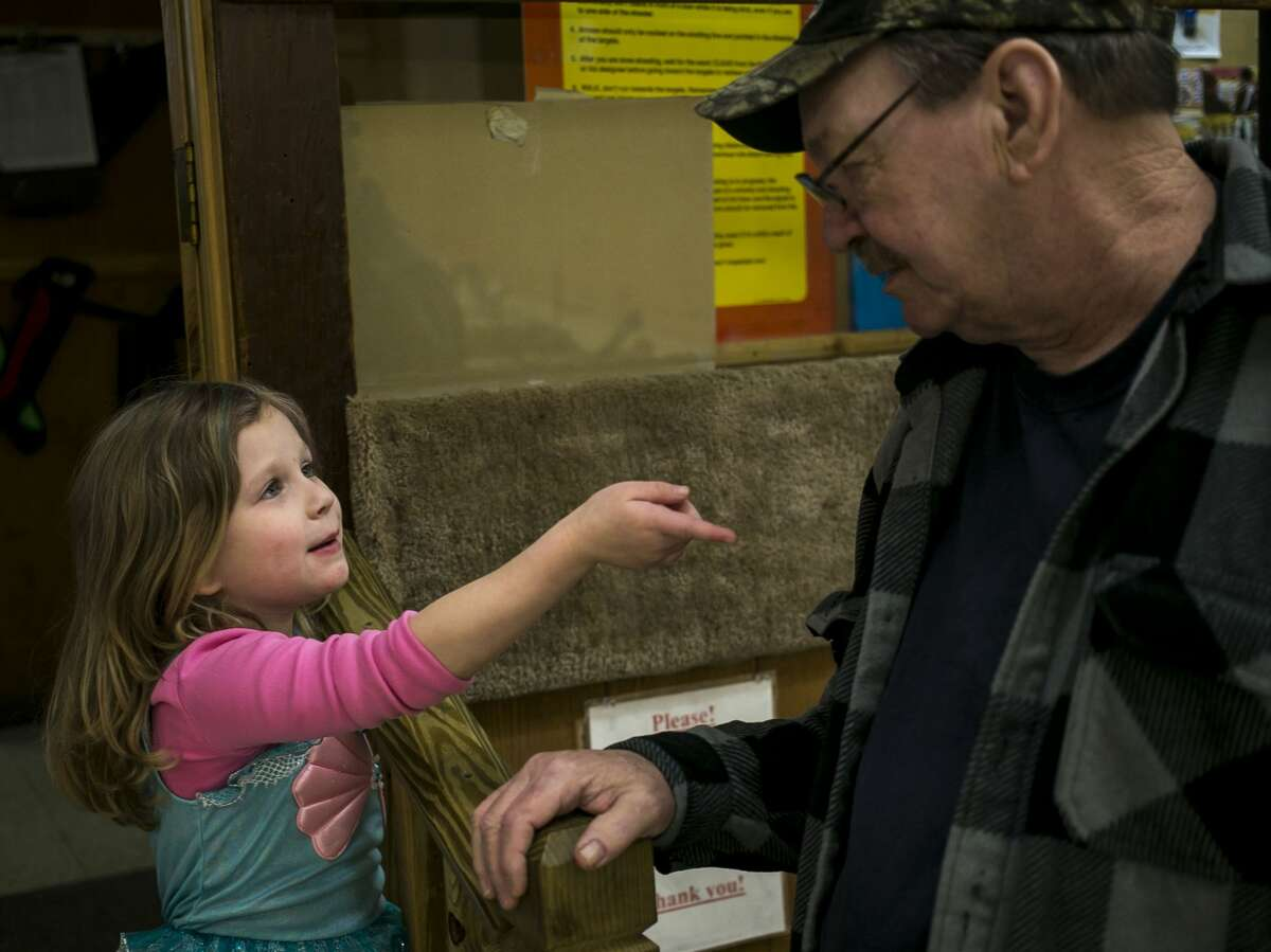 Kylie Church, 5, of Midland chats with Joel Cermac of Merrill during the Youth Indoor 3D shoot at Mid Michee Bowmen Saturday, Feb. 17, 2018. (Josie Norris/for the Daily News)