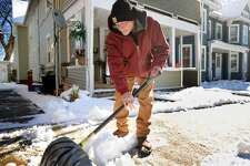 Recovering from a recent hip transplant and also a hernia, Keith Wimberly clears snow from his neighbors front walk in Derby, Conn. on Sunday, February 18, 2018.