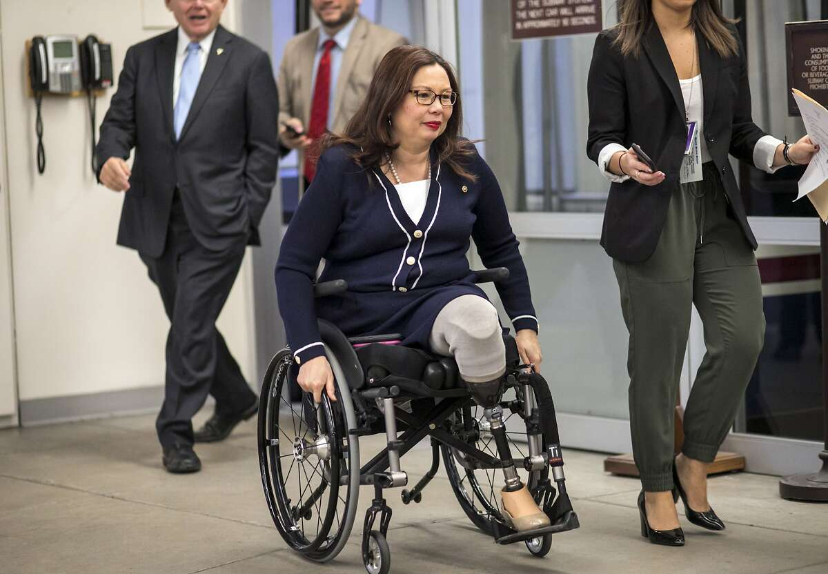 Sen. Tammy Duckworth, D-Ill., and other senators arrive to vote on the confirmation of Samuel Brownback, governor of Kansas and a former U.S. senator, to become the ambassador-at-large for international religious freedom, at the Capitol in Washington, Wednesday, Jan. 24, 2018.