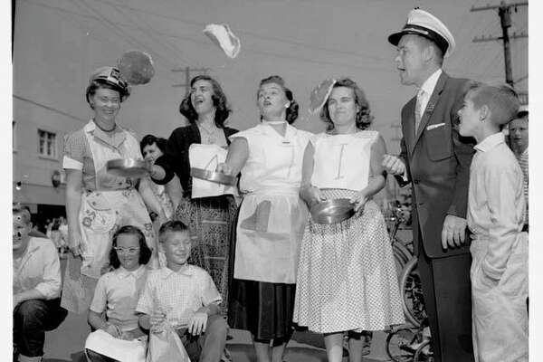 Participants of the 100-yard pancake race pose with the mayor of White Center, Gordon S. Clinton, who judged the event. In the contest, married women had to flip a pancake three times over in a skillet while racing 100 yards down the middle of 16th Avenue Southwest. The winner was Mrs. Gladys Pingatore, shown here standing the the left of the mayor. The race was part of the Pancake Festival, sponsored by the White Center Eagles in 1956.  Courtesy of MOHAI