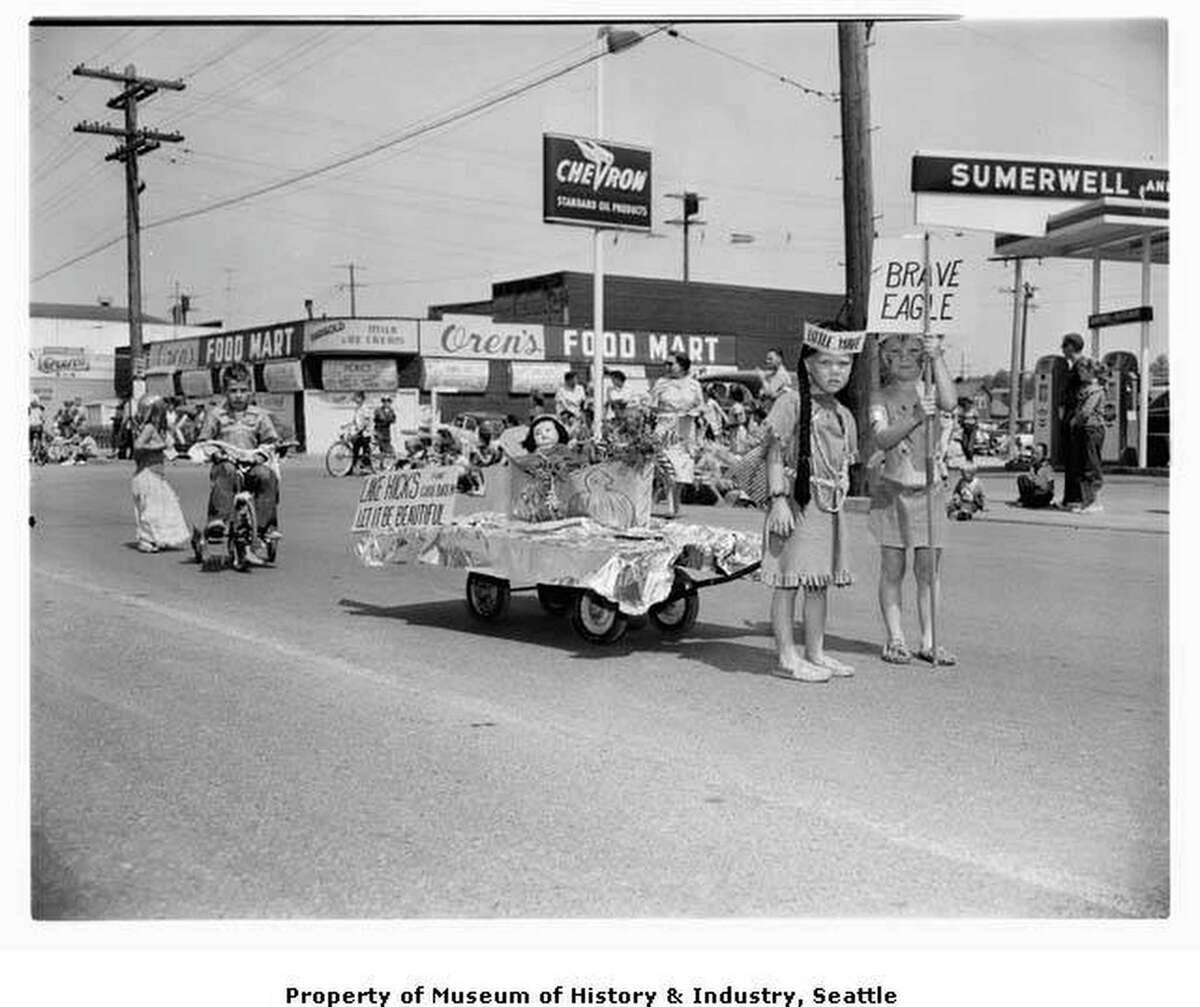 White Center's 1956 Pancake Festival, sponsored by the White Center Eagles, hosted races, parades and other community events. In the children's parade, two youngsters dressed in Native American costume pull a wagon with a doll and a sign reading: Lake Hicks for Children, Let It Be Beautiful. A young boy on a tricycle follows behind. Courtesy of MOHAI