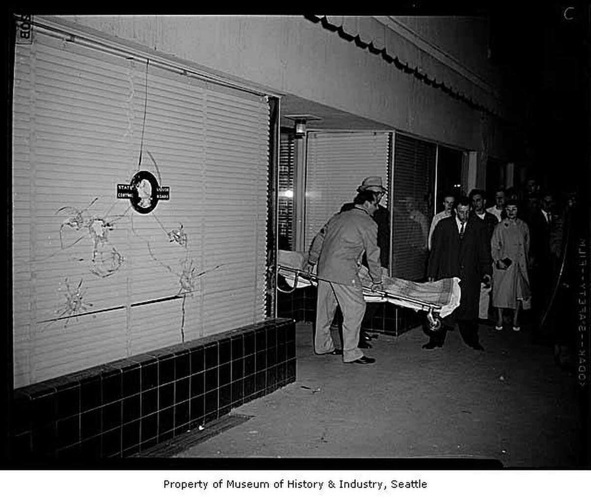 Two robbers forced their way into the White Center State Liquor Store after closing time on Saturday night, April 4, 1959. Three store employees were forced to lie on the floor behind the counter while the chief clerk of the store, Gino Giuntoli, stalled for time while opening the safe at gunpoint. King County deputies Jack Triplett and Jim Foley and reserve deputies M. A. Christopherson and William Hayden arrived on the scene while the robbery was in progress. Christopherson and Triplett entered the rear of the store and fired at the robbers in front of the store counter. One of Triplett's bullets fatally wounded Michael L. Mooney, 48. After a shootout on the sidewalk with the other two officers, the second robber fled the scene with $2,000 of the $6,000 taken from the safe. Mooney's body was covering a cardboard box containing $4,000 of the loot. In this image, the body of liquor store bandit Michael L. Mooney is carried on a stretcher from White Center State Liquor Store at 10034 16th Ave. SW by King County Coroner Leo Sowers (foreground, in jacket) and his deputies. Note the plate glass window at left, riddled with bullet holes.