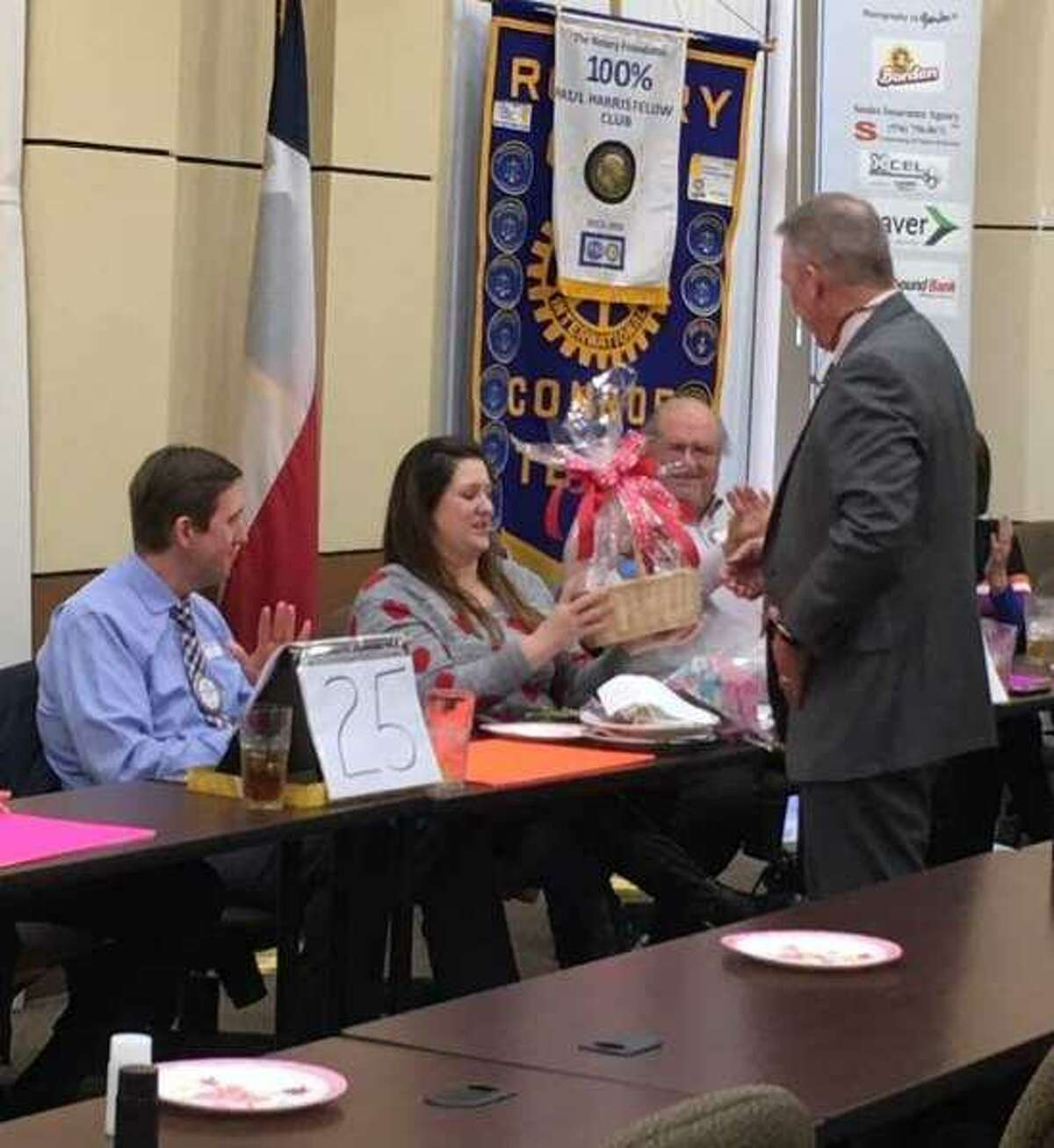 """Master of Ceremonies Denny Buckalew, with his back to the camera, presents a gift basket to Rotarian Nick Davis and his wife Kara after they won the """"Not So Newlywed Game"""" at last week's Rotary Club of Conroe special Valentine's week meeting."""