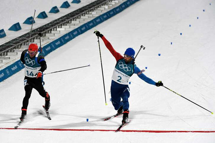 Martin Fourcade of France, right, slides a ski over the finish line to pass Simon Schempp of Germany  to win gold in the men's biathlon 15km mass start during the 2018 Winter Olympics at the Yongpyong Alpine Centre in Peyongchang, South Korea, Feb. 18, 2018. (James Hill/The New York Times) -- NO SALES --