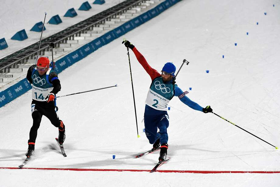 Martin Fourcade slides a ski over the finish line to pass Simon Schempp to win the biathlon 15 kilometer mass start. Photo: JAMES HILL, NYT