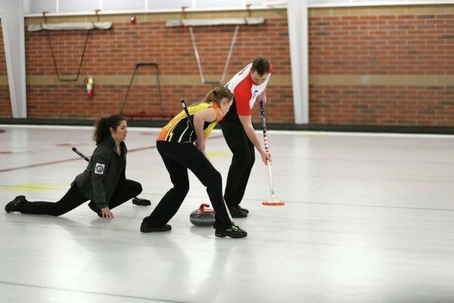 Julia DiBaggio of Mayfield Curling Club, Harley Rohrbacher of Mayfield Curling Club and Guy Davis of Lone Star Curling Club compete during the Great Lakes Curling Association's Mixed Curling Championship at the Midland Curling Center in Midland on Sunday, Feb 19, 2018. (Samantha Madar/for the Midland Daily News)