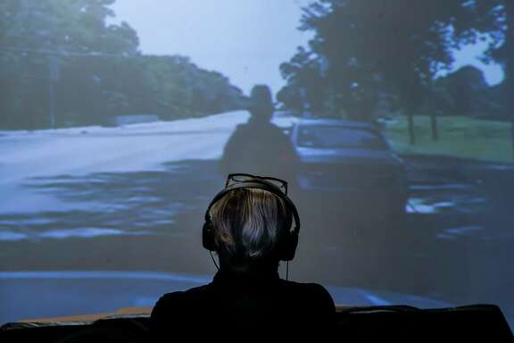 """Pat Jasper watches the dash cam video of Sandra Bland being pulled over and arrested before she died in custody in 2015 at an exhibition about Bland at the Houston Museum of African American Culture Monday, Feb. 5, 2018 in Houston. """"It's important during these times that this information gets out,"""" said John Guess Jr., Houston Museum of African American Culture CEO and curator of the exhibition. """"Here's this family, and after a tragedy they become symbols and nothing else. I wanted to say that from Texas, we understood the pain that happened here."""" The show runs through the month of February."""