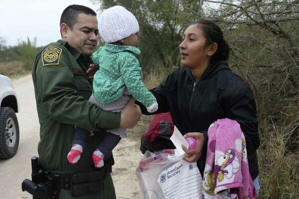 U.S. Border Patrol Agent Marcelino Medina hands over seven-month-old Allison Valera, to her mother, Katerine Valera, 20, after they surrendered to agents near the Anzalduas International Bridge in Hidalgo County, Monday, Feb. 12, 2018. They were with four other Honduran immigrants that surrendered to the agents. Immigrants are required to remove their belts and shoelaces before they are transported to detention facilities and Medina was holding the infant as the mother complied.