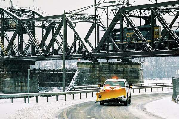 "A plow truck passes under the Livingston Avenue Bridge in Albany during the Feb. 7 snowstorm in this photo by Mark DuMont of Colonie. He?s a teacher at Averill Park and school had been canceled due to the snow. This is how the photo transpired, he says: ""I like to use film, and I needed to take a few pictures to finish a roll. I went down to the parking area under 787 hoping to capture how the snow might change that familiar riverfront, when I heard the train coming and snapped this picture just as a snow plow came under the bridge while the train passed over."""