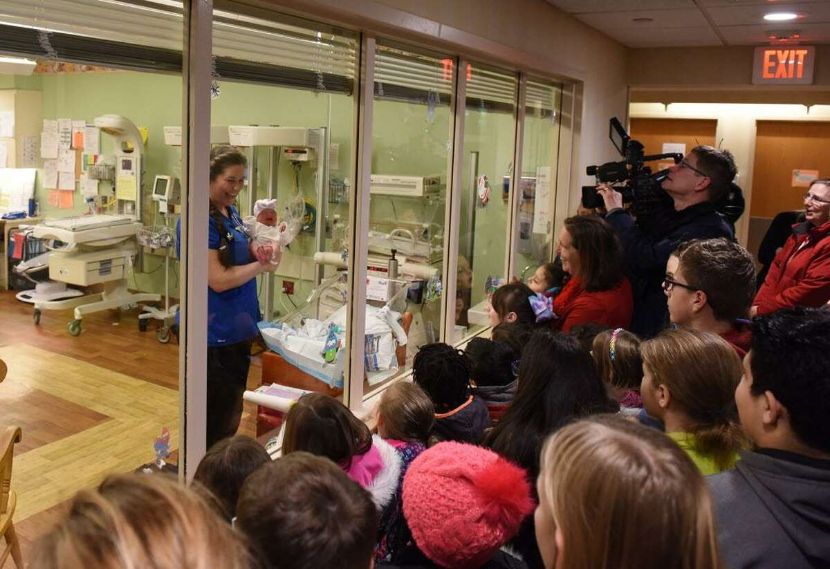 Each year, kindergartners in teacher Gretchen McInvales' class at Spencer Elementary School in Middletown travel to St. Francis Hospital and Medical Center's maternity ward to deliver items. Here, nurse Tracey Mitchell shows off a newborn.