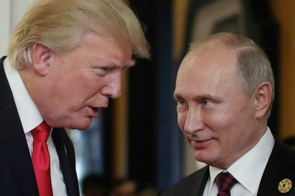 "(FILES) In this file photo taken on November 11, 2017 US President Donald Trump (L) chats with Russia's President Vladimir Putin as they attend the APEC Economic Leaders' Meeting, part of the Asia-Pacific Economic Cooperation (APEC) leaders' summit in the central Vietnamese city of Danang. The US special prosecutor investigating Moscow's meddling in the 2016 presidential election on February 16, 2018 indicted 13 Russians for allegedly running a secret campaign to tilt the vote, prompting claims of vindication from President Donald Trump.The indictment -- which includes the first charges laid by special counsel Robert Mueller for election interference -- detailed a stunning operation launched in 2014 in a bid to sow social division in the US and influence American politics ""including the presidential election of 2016.""  / AFP PHOTO / SPUTNIK / Mikhail KLIMENTYEVMIKHAIL KLIMENTYEV/AFP/Getty Images"