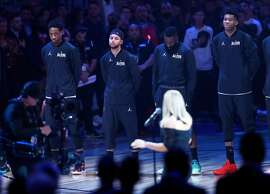 Golden State Warriors' Stephen Curry listens as Fergie sings National Anthem before NBA All Star Game at Staples Center in Los Angeles, Calif., on Sunday, February 18, 2018.