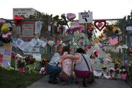 From left: Shari Unger, Melissa Goldsmith and Giulianna Cerbono embrace outside Marjory Stoneman Douglas High School on Sunday.
