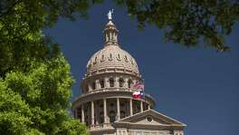 An American flag flies with the Texas state flag outside the Texas State Capitol building in Austin, Texas, U.S., on Wednesday, March 15, 2017. Austin has spent the last 10 months engaged in a big experiment in urban transportation. Several hundreds of thousands of people will descend upon Austin for the annual South by Southwest festival, a nine-day event that could be described as a tech conference, a music and film festival. Photographer: David Paul Morris/Bloomberg