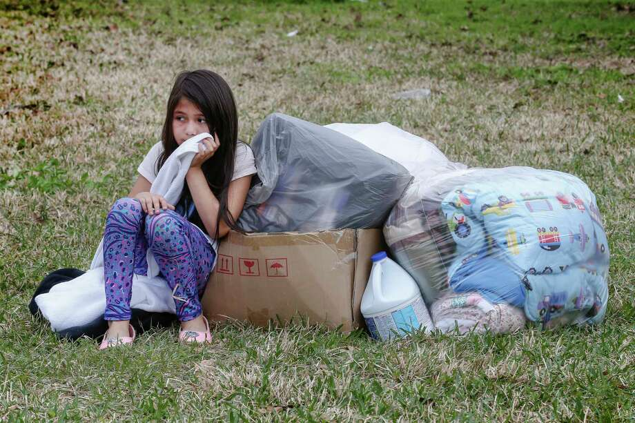 Kimberly Rodgz, 6, waits with a stack of donated items as her mother picks out clothes Sunday in north Houston. About 400 people benefited from the work of a group of volunteers who aid Harvey victims still in need of help six months after the hurricane. Photo: Steve Gonzales, Houston Chronicle / © 2018 Houston Chronicle