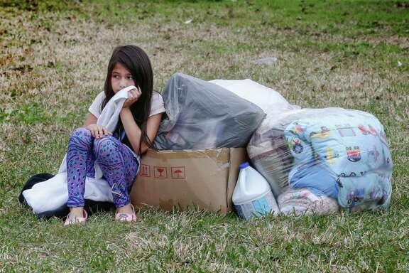 Kimberly Rodgz, 6, waits with a stack of donated items as her mother picks out clothes Sunday in north Houston. About 400 people benefited from the work of a group of volunteers who aid Harvey victims still in need of help six months after the hurricane.