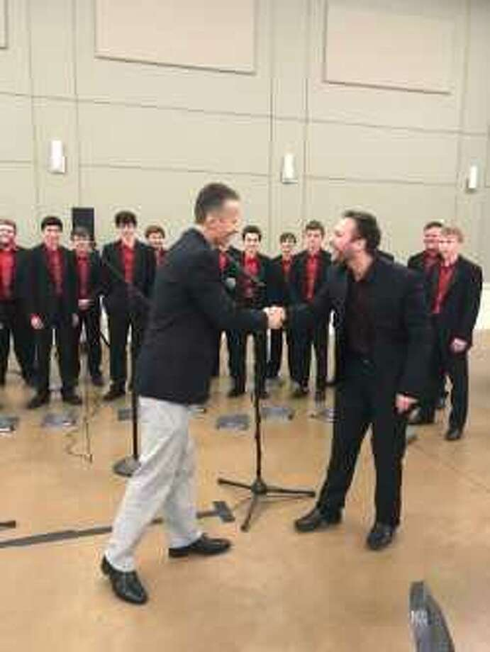 Program Chair Mike Sproba, left, thanks Cameron Carnley, Director of the Montgomery High School Men's Chorale for their performance during the Conroe Noon Lions Club annual Sweetheart's Day. Photo: Submitted Photo