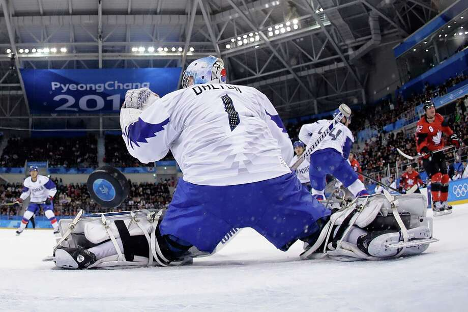The puck flies past South Korea goaltender Matt Dalton as Canada's Christian Thomas scores in his team's 4-0 victory, which sent the Canadians into the quarterfinals of the hockey tournament. Photo: JULIO CORTEZ, Contributor / AFP