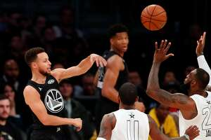 Team Stephen's Stephen Curry passes over Team LeBron's LeBron James as Kyrie Irving watches duiorng Team LeBron's 148=145 win during NBA All Star Game at Staples Center in Los Angeles, Calif., on Sunday, February 18, 2018.