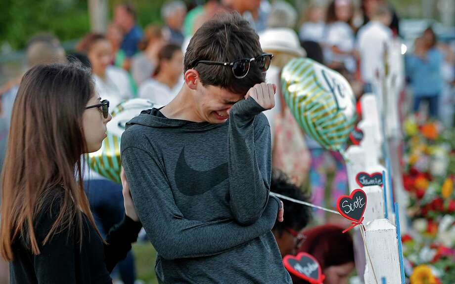Daniel Bishop, 16, a student at Marjory Stoneman Douglas High School, cries at a makeshift memorial outside the school, in Parkland, Fla., Sunday, Feb. 18, 2018.  Photo: Gerald Herbert, AP / Copyright 2018 The Associated Press. All rights reserved.