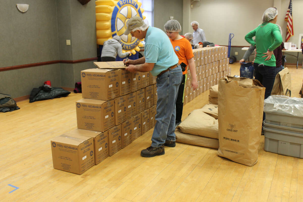 Bags and tubs of grain, right, sit ready for distribution while boxes of finished meals are stacked, left, at the front of the lodge hall.