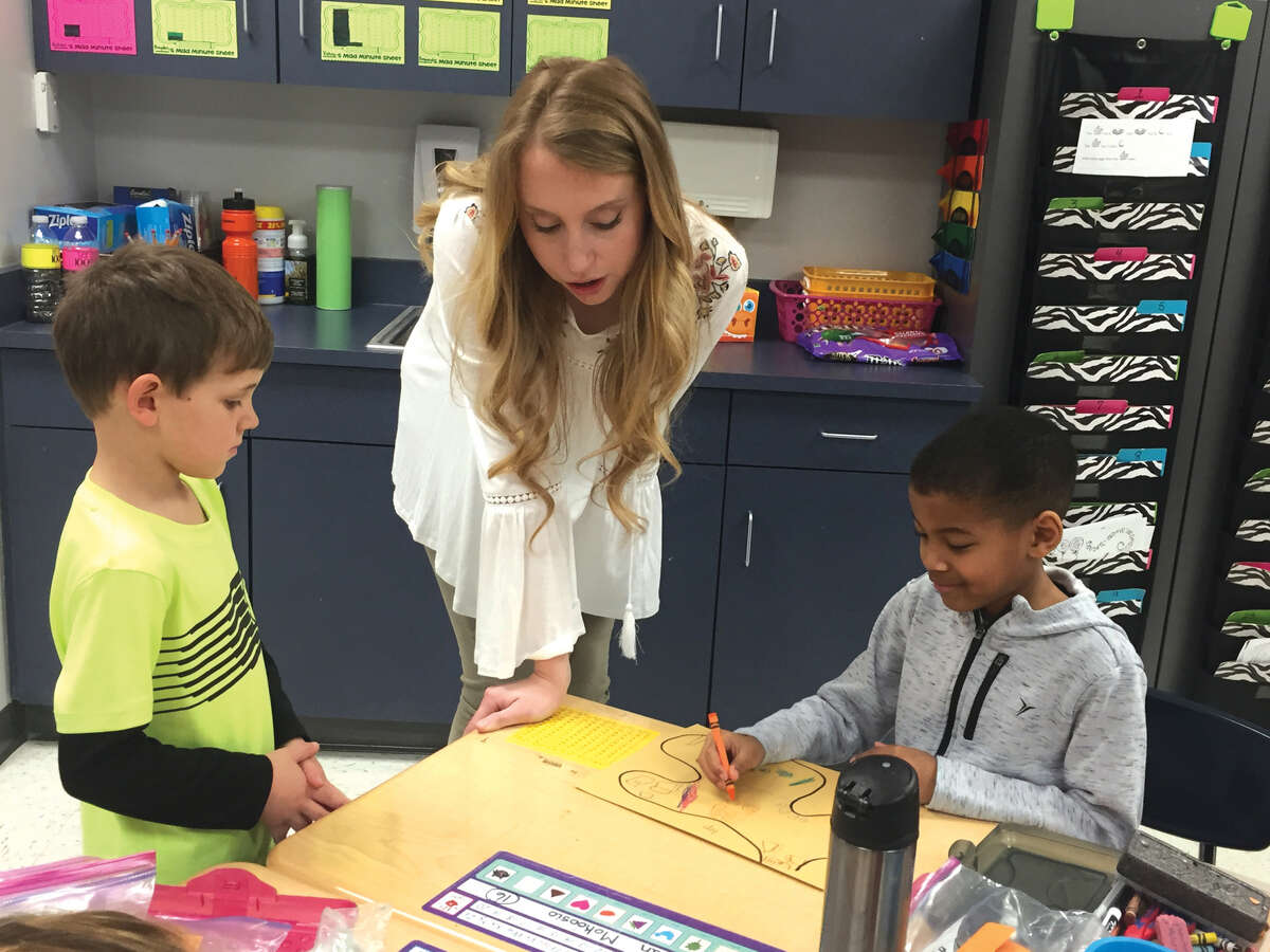 Student teacher Faith Gilchrist, center, works with Goshen Elementary first graders Michael Becker, left, and Christion Mokoosio.