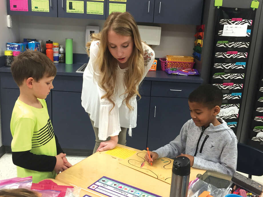 Student teacher Faith Gilchrist, center, works with Goshen Elementary first graders Michael Becker, left, and Christion Mokoosio. Photo: Julia Biggs • Jbiggs.edwi@gmail.com