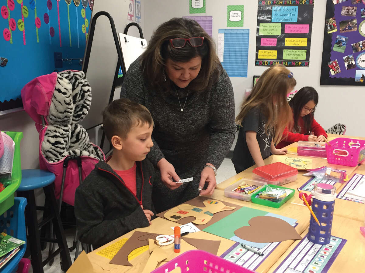 Goshen Elementary first grade teacher Pam Jarvis works with Henry Bailey on a project.