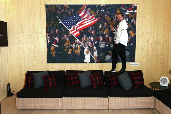 U.S. Olympian Joe Polo signs the athlete wall at the USA House at the 2018 Winter Olympic Games in South Korea. A reader is heartened that U.S. athletes are honoring the flag.